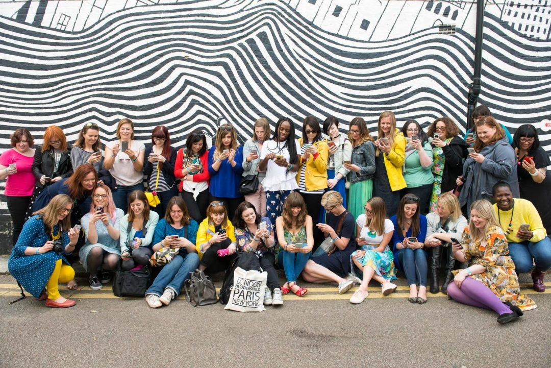 group of Blogtacular attendees in front of a stripey wall