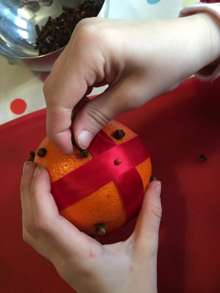 placing cloves in an orange