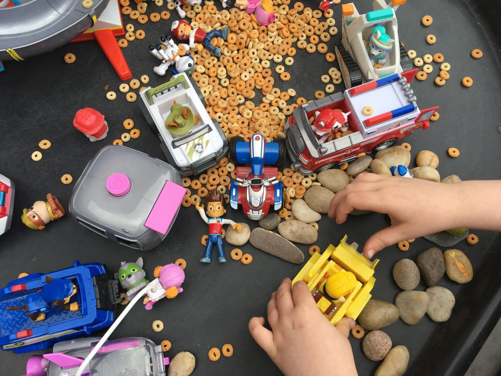 I helped them place the stones in the tuff spot, along with some of their Paw Patrol toys. Then poured some of the cereal into a container. This is what it looked like.