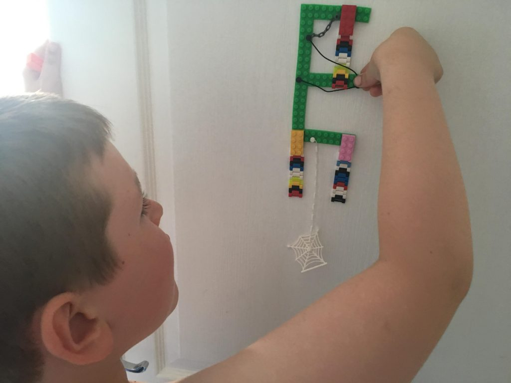 boy adding to lego tape on bedroom door