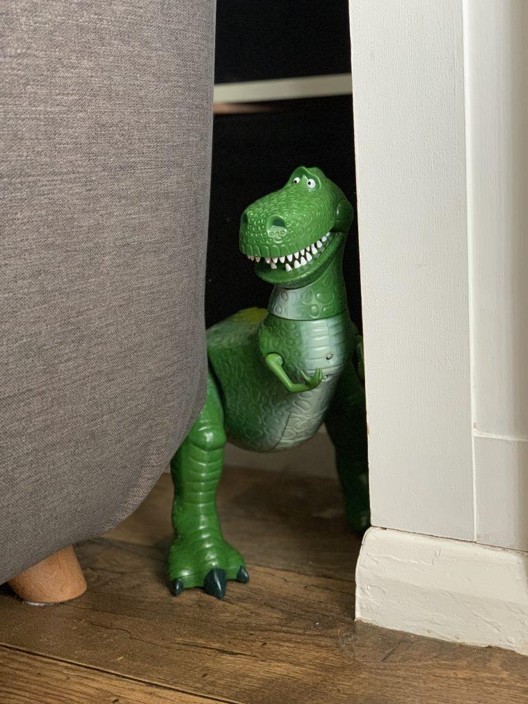 Rex hiding behind the sofa