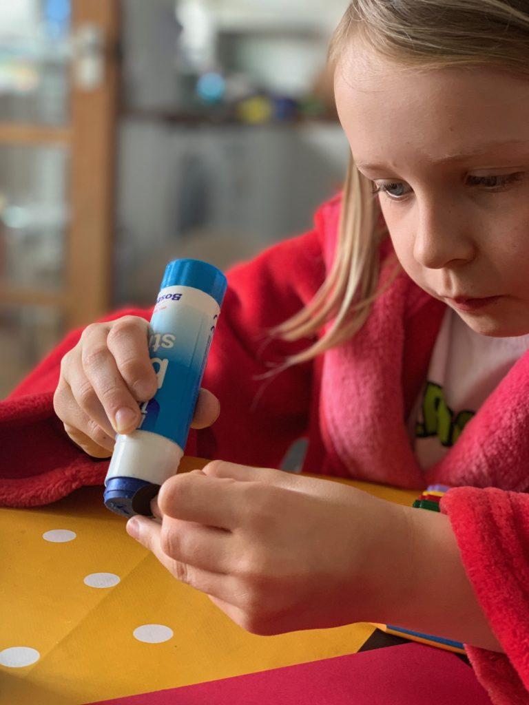 child using a glue stick