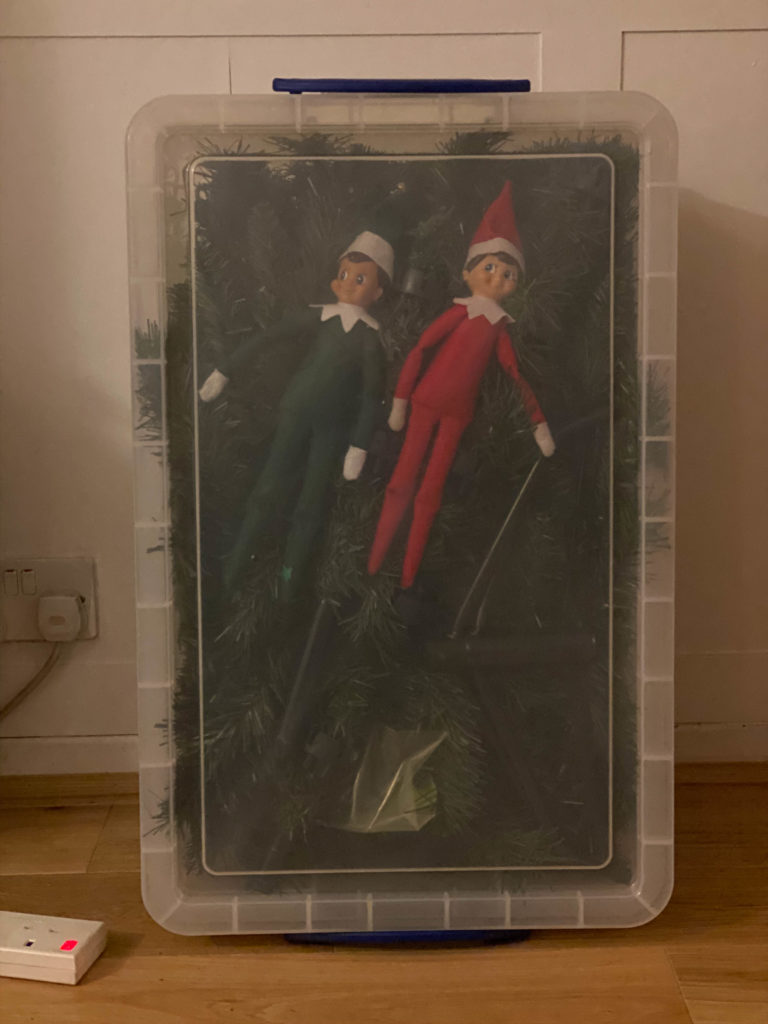 Elf on the Shelf hiding inside the Christmas decorations box
