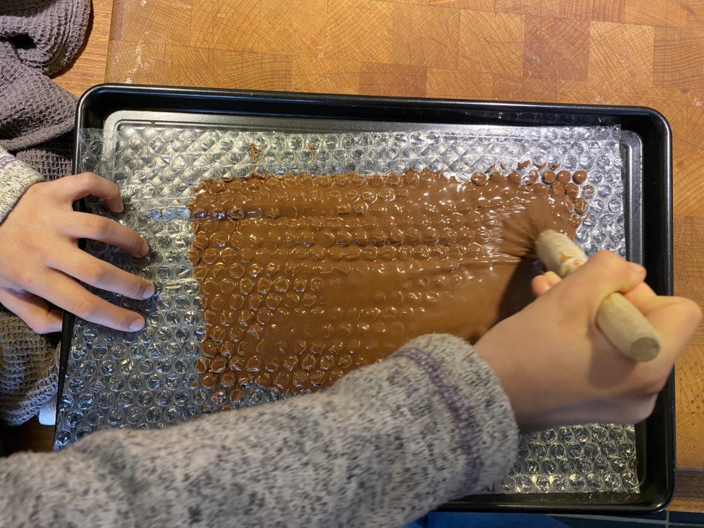 brushing chocolate over bubble wrap